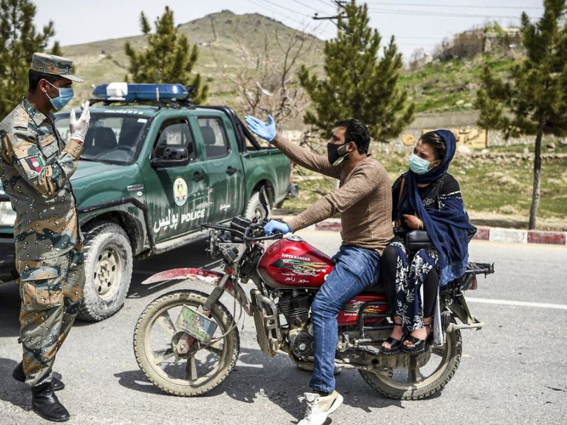 Afghans at an Afghanistan police checkpost in times of COVID 19 pandemic